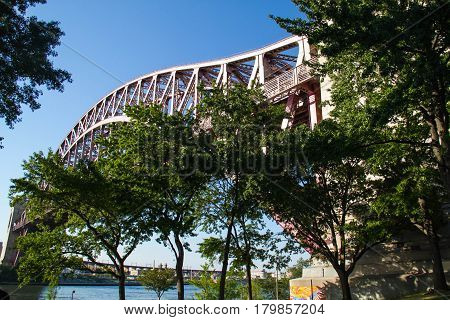 Hell Gate Bridge over the river and trees with blue sky at Astoria park, New York