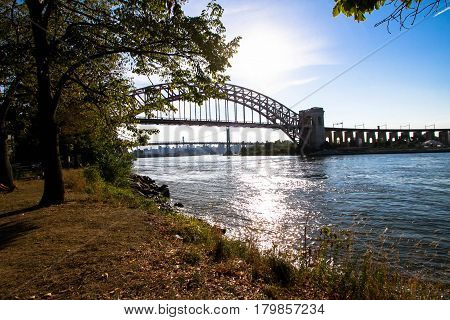 The Hell Gate Bridge over the river at Astoria park, New York