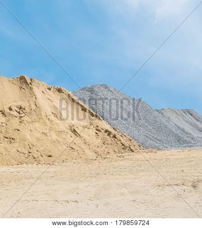 Closeup pile of sand and stone for construction work with ground and blue sky textured background