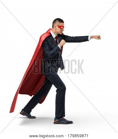 A businessman in a superhero red cape and a mask standing in side view in punch position on white background. Business and success. Competition battle. Fighting off adversaries.