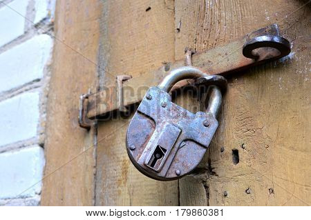 Iron lock with the bolt on the opened wooden door