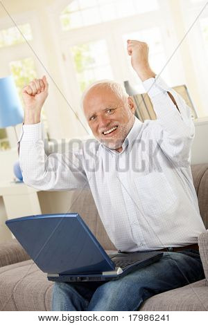 Happy old man sitting on sofa with laptop, raising arms and laughing, looking at camera.