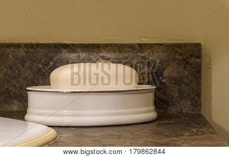 Bar Of White Soap In Dish Sitting On Dark Washbasin
