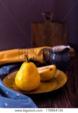 fresh ripe pears in yellow plate on old dark wood background