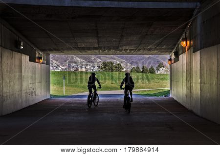 Two people riding their bicycles through a tunnel with a beautiful view ahead