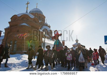 Kazan, Russia - 28 february 2017 - Sviyazhsk Island : The pancake week - Russian ethnical carnival Maslenitsa, Shrovetide, the crowd carries the effigy of winter to burn - in front of church, snow sunny day