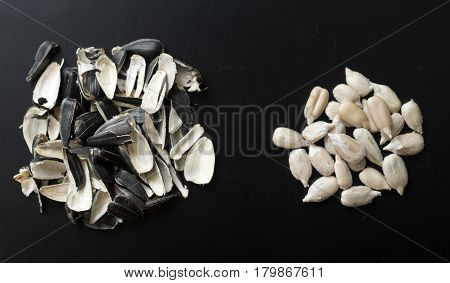 sunflower seeds and husks on black background