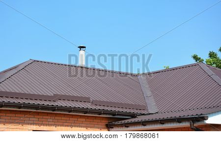 Metal roofing construction with gutter system and asbestos chimney