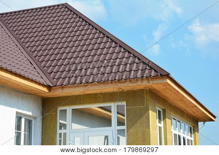 Roofing Construction. House wall repair renovation insulation detail. Building insulation exterior added to buildings for comfort and energy efficiency. Rain Gutter. Soffit and Fascia installation.