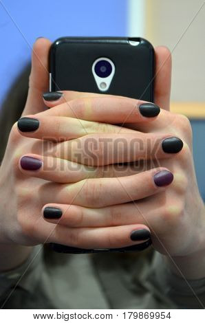 Hands with manicure - black and purple gel polish with a matte top