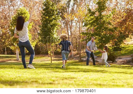 Family Playing With Disk In Park Together