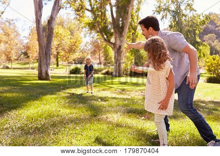 Father With Children Throwing Disk In Park Together
