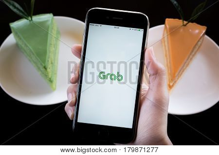 CHIANG MAITHAILAND - JAN 292017 : A MAN hand holding Grab app showing on iphone 6s with Matcha green tea and ice tea cake in coffee shop. Grab is smartphone app-based transportation network