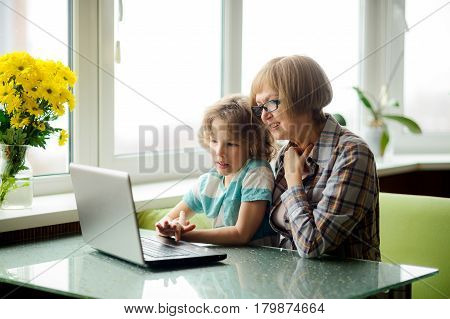 The grandmother and the grandson with interest look at the laptop screen. The elderly woman and the boy sit next. Modern technologies are available to people of all age.