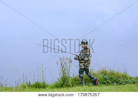 Boy Fishing At The Side Of Beauty Lake