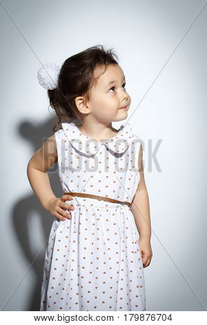 Portrait of 3 year old little girl with dress, looking up on bright white background
