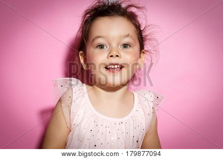 Portrait of Happy 3 year old little girl with dress, smiling on bright pink background