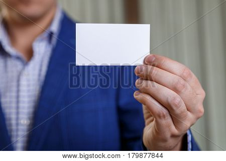 Businessman holding visit card. Man showing blank business card. Person in blue suit. Mock up design.