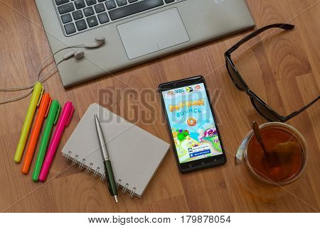 Nitra, Slovakia, april 3, 2017: Pac Man Bounce application in a mobile phone screen. Workplace with a laptop, an earphones, notepad, pen, tea, sunglasses and color markers on wooden background