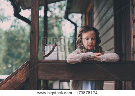child girl with candle holder relaxing in evening at cozy country house. Kid spending summer vacation in log cabin in the woods