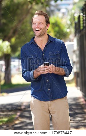 Smiling Handsome Man Walking With Cell Phone