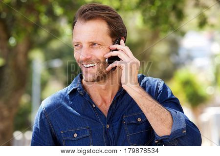 Handsome Man Smiling With Mobile Phone Outdoors