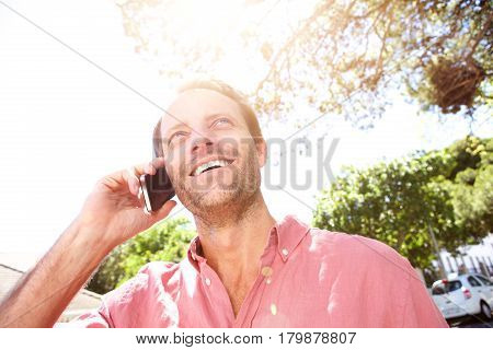 Smiling Older Man Outside With Mobile Phone