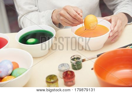 Hands of the woman preparing and dying Easter eggs