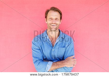 Handsome Man Smiling Against Pink Wall