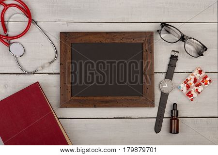 Blank Blackboard, Pills, Book, Stethoscope, Eyeglasses And Watch On Wooden Background