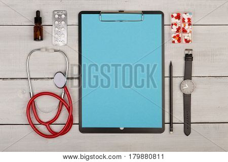 Blank Clipboard, Pills, Stethoscope And Watch On Wooden Background