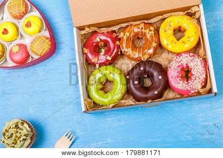 Glazed donuts, cupcakes and macaroons. Sweet dessert in delivery box. Cakes with buttercream. Almond macaron cookies.