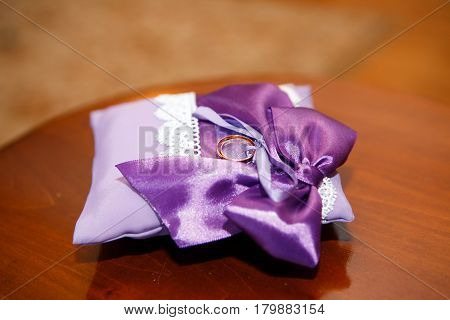Weddings ring on the serenity pillow on a brown background