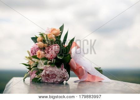 Wedding bouquet from pink pions and roses