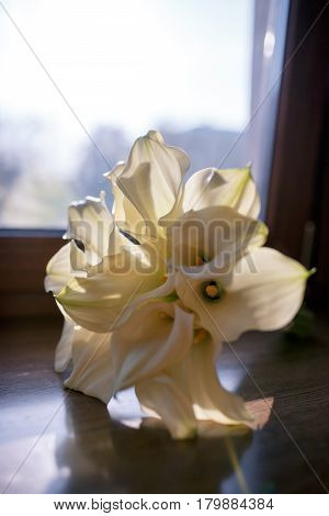 Wedding bouquet of white calla flowers on the table