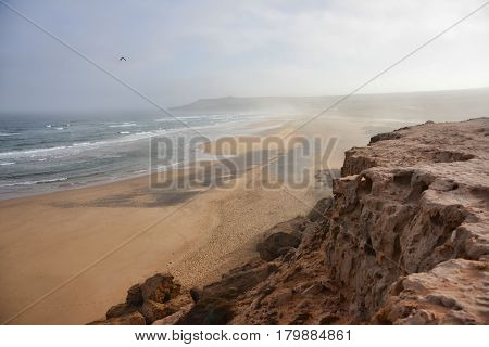 Coast band connects the mountains and the ocean. The picture shows the Atlantic Ocean waves at low tide. Coast and Mountains.