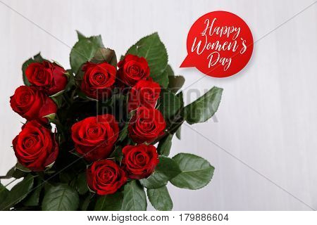 Red roses on white wood vintage background. Happy Womens day speech bubble. 8 march or Valentines day love design. Painted wooden planks.
