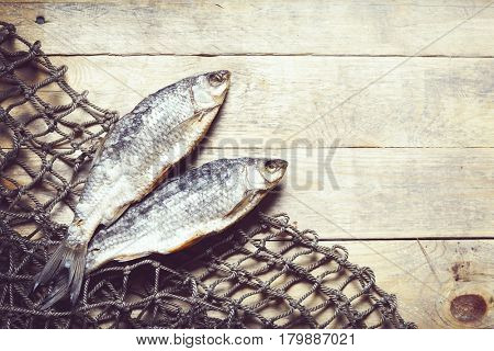 Sun dried fish and fishing nets on the wooden background.