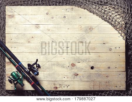 Fishing nets and fishing rod still-life on the wooden background.