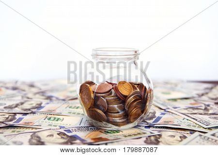 Glass jar with coins on the white background. A lot of dollar bills