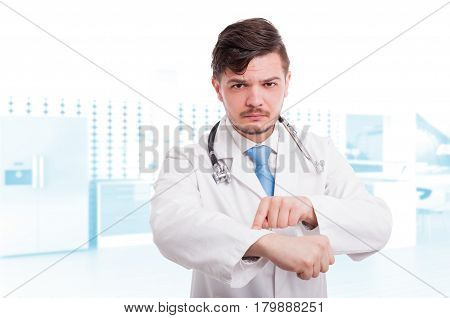 Serious Male Doctor Pointing His Wrist Watch