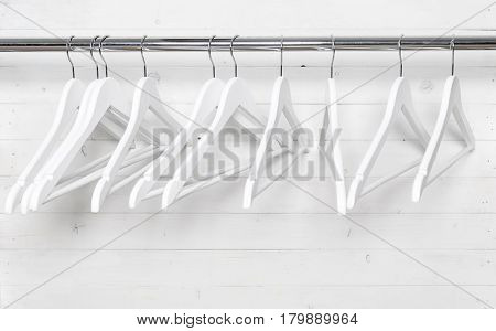 Hangers on the rack placed sort of chaotically, all white with black hooks