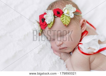Sweet girl in bright Ukrainian colorful hairband and a white suit sleeps tight on her side