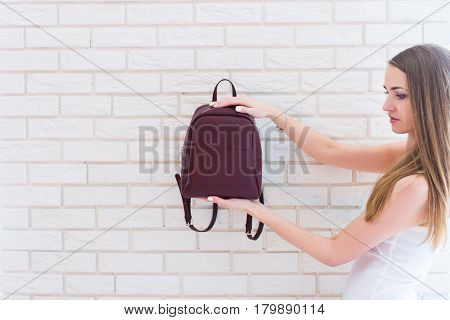Caucasian beautiful girl with long brown present a backpack of marsala color.