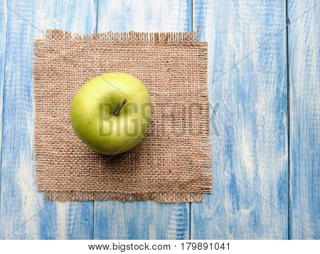 green apple on a blue wooden table