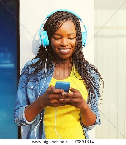 Fashion Pretty Smiling African Woman In A Headphones Listens To Music Using Smartphone In The City
