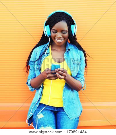 Fashion Pretty Smiling African Woman With Headphones Listens To Music Over Orange Background