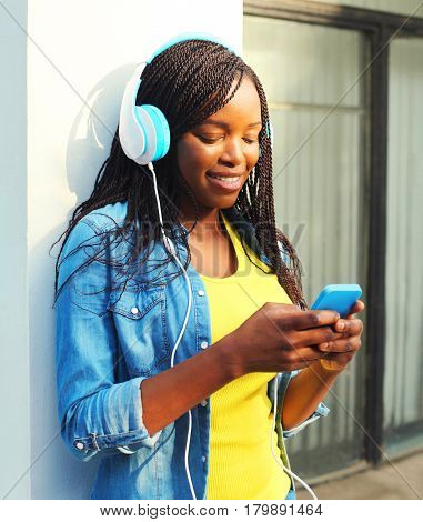Fashion Pretty Smiling African Woman With Headphones Listens To Music Using Smartphone In The City