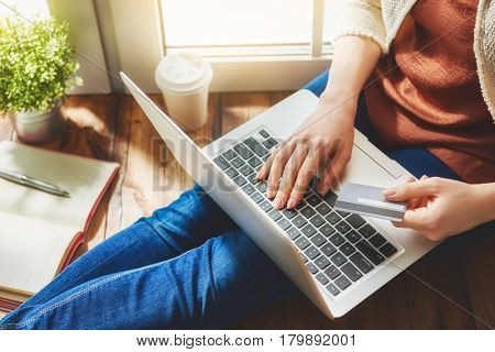 Woman is holding credit card and using laptop computer. Online shopping concept. Close up.