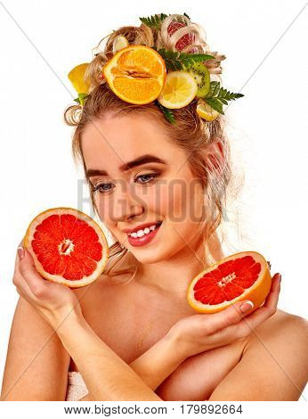 Hair mask from fresh fruits on woman head. Girl with beautiful face holds halves of grapefruit for homemade organic skin and hair therapy. Concept of hydrating healthy and beauty hair and skin.